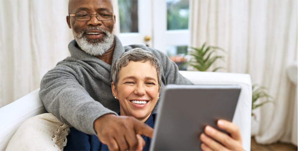 Older couple sitting on the couch with a computer tablet